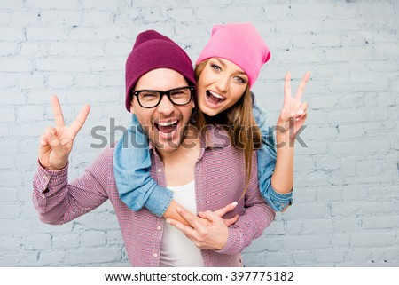 Happy cheerful man and woman embracing, gesturing with two fingers and screaming