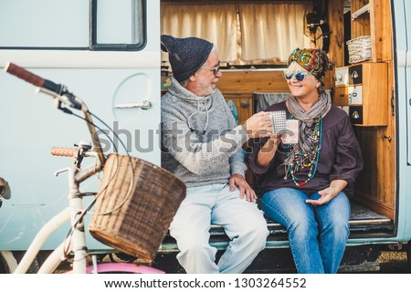 Happy cheerful mature people couple caucasian traceler enjoy and take a break resting sit down out of her van during alternative vacation for nice retired lifestyle together forever with love