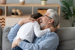 Happy cheerful old senior grandpa embracing cute little boy grandson laughing cuddling at home, two 2 generations family elder grandfather and small grandkid hugging bonding playing sit on sofa