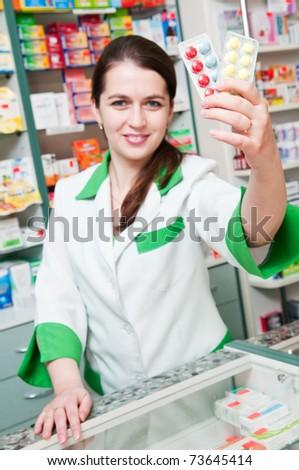 Happy cheerful pharmacist chemist woman standing in pharmacy drugstore with pills