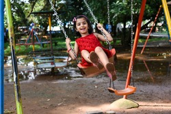 Happy cheerful smiling cute little girl/ child/ kid swinging in park, Kerala, India. Naughty playful young Indian daughter enjoying evening day out, on rainy day on vacation. Playing school play area