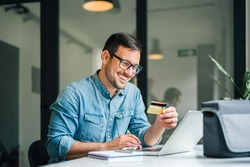 Happy cheerful smiling young adult man doing online shopping or e-shopping satisfied entrepreneur making online payment paying for service or goods self employed freelancer collecting fee paying happy