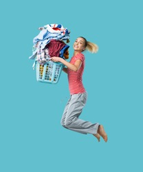 Happy cheerful woman doing laundry and jumping, she is holding a laundry basket filled with clothes