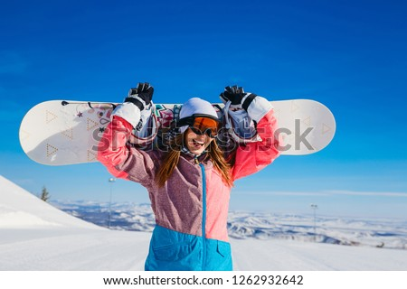 3b75b5681cd happy cheerful woman in a ski suit and glasses holds a snowboard in her  hands in