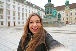 Happy cheerful woman in Vienna at winter time. Travel in Europe girl take self portrait in Hofburg courtyard in Vienna, Austria.