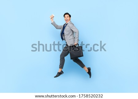 Happy cheerful young Asian businessman jumping while holding bag and coffee cup in isolated studio blue background