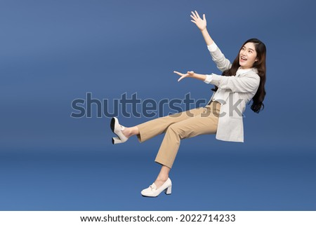 Happy cheerful young Asian businesswoman in suit floating in the air isolated on blue background, Presentation concept