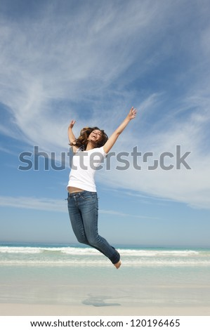 Happy cheerful young attractive woman jumping full of joy at beach with arms up, isolated with ocean and blue sky as background and copy space.