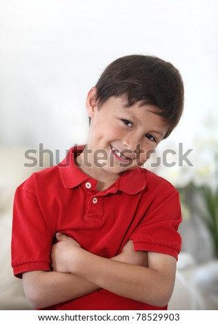 Happy cheerful young Latino or Hispanic school boy in red shirt against light background in portrait mode with copy space on top