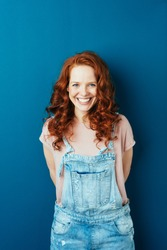 Happy cheerful young redhead woman in dungarees standing over a dark studio background with copy space grinning at the camera