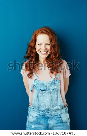 Happy cheerful young redhead woman in dungarees standing over a dark studio background with copy space grinning at the camera #1069187435