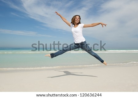 Happy cheerful young sexy woman jumping full of joy at beach with arms up, isolated with ocean and blue sky as background and copy space.