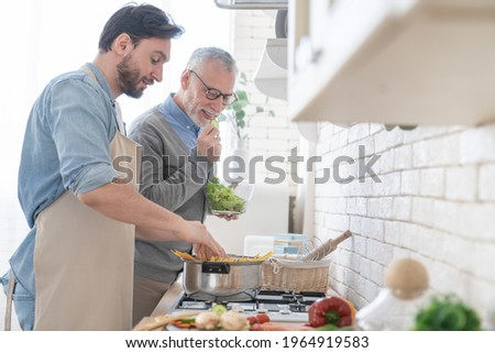 Happy cheerful young son helping his old senior father in preparing meal, food, dinner, lunch in the kitchen. Family time, cooking together. I love you, dad! Happy father`s day!