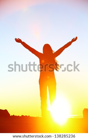Happy cheering celebrating success woman at beautiful sunset above the clouds. Girl enjoying view of colorful sunset with arms raised up towards the sky. Happy free freedom concept image outdoors.
