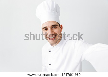Happy chef cook wearing uniform standing isolated over white background, taking a selfie