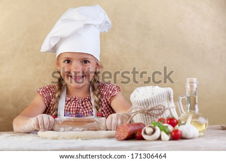 Happy chef little girl stretching the dough - with food ingredients on the side of table