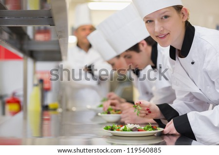 Happy chef looking up from preparing salad in culinary class