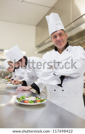 Happy chef with others preparing salads in the kitchen