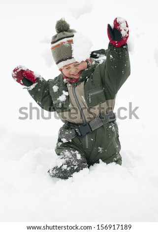 Happy chiild toddler, boy or girl, in snow licking  his cold hands  in winter.