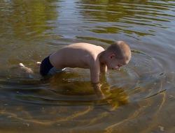 Happy child. A child bathes in the clear water of the Volga River