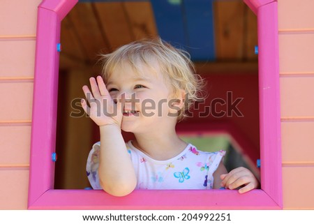 Happy child, adorable blonde toddler girl, having fun outdoors hiding in plastic playhouse in playground on a sunny summer day