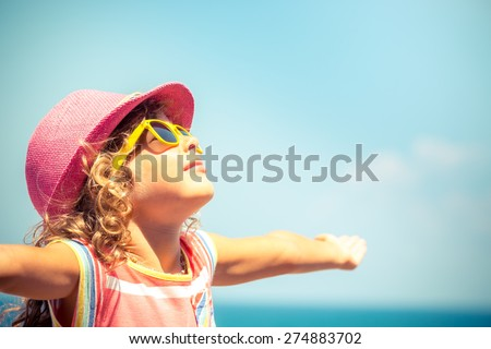 Happy child against blue sky background. Summer vacation concept