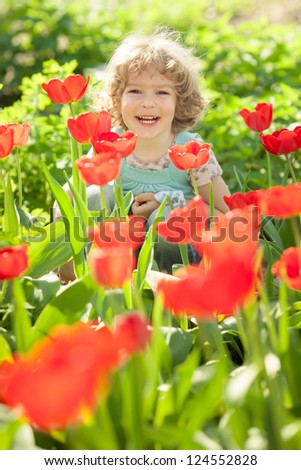 Happy child against spring flowers background