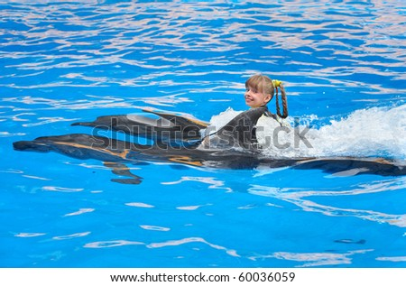 Happy child and dolphin swimming in blue water.