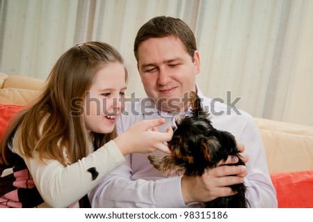 Happy child and her father are playing with dog at home