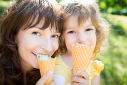 Happy child and mother eating ice-cream outdoors in summer park
