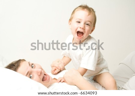 Happy child and mother wearing white attire in white bed and room. - stock photo