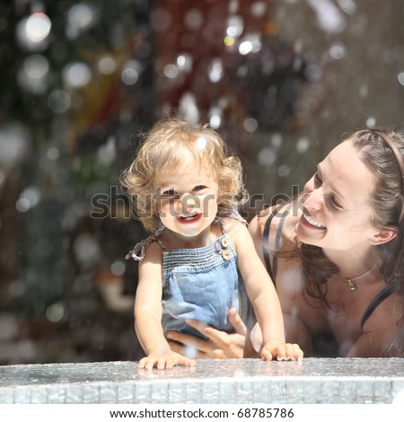 Happy child and woman in fountain splashes