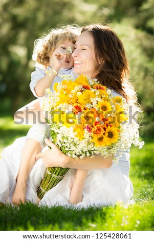 Happy child and woman with bouquet of spring flowers sitting on green grass. Mother`s day concept - stock photo