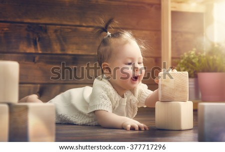 happy child  baby girl playing with blocks and having fun. stock photo