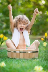 Happy child bathing outdoors on green grass in spring garden