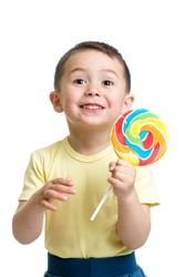 Happy child boy eating big candy lollipop isolated on white background