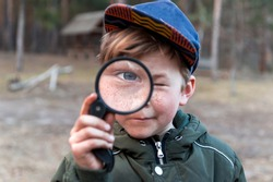 Happy child boy exploring nature with magnifying glass. Kid discovering world in part on spring and summer time. Forest school.