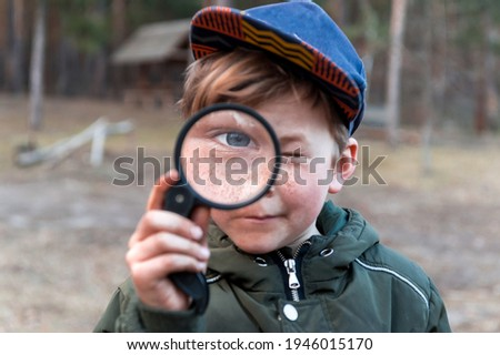 Happy child boy exploring nature with magnifying glass. Kid discovering world in part on spring and summer time. Forest school. Foto stock ©