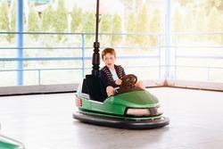 Happy child boy having fun in amusement park. Taking a ride on bumper car.