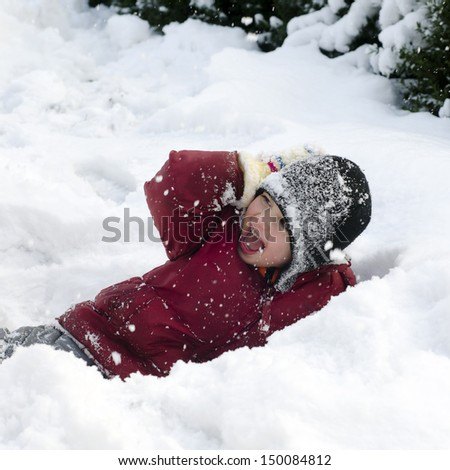 Happy child, boy or girl, playing in a deep fresh snow in winter.