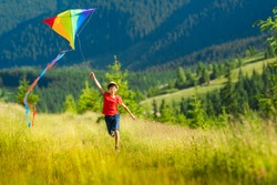 Happy child boy with a kite running on meadow in summer in nature. Mountain landscape in the background. Boy wearing hat, red t-shirt and shorts. Copy space.