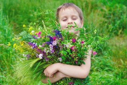Happy child boy with bouquet of wild flowers in his hands enjoying by Summer