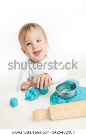 happy child building fine motor skills with play dough or play clay