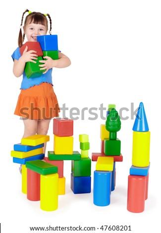 Happy child builds a castle out of color blocks