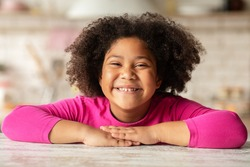 Happy Child. Closeup Portrait Of Cheerful Cute Little Black Girl Sitting At Table In Kitchen, Laughing African American Female Kid Relaxing At Home, Looking At Camera And Smiling, Free Space