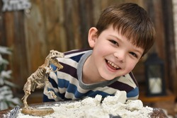 Happy child digging the dinosaur and having fun with archaeology excavation kit. Boy plays an archaeologist excavated, training for dig fossil