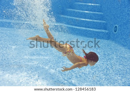 Happy child diving underwater in swimming pool beautiful healthy girl swims and having fun in water Kids sport on family summer vacation Active holiday