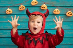 Happy child dressed Halloween costume. Portrait of funny kid against wooden background.