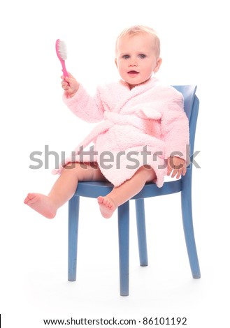 Happy child dressed in bath robe with hair brush.