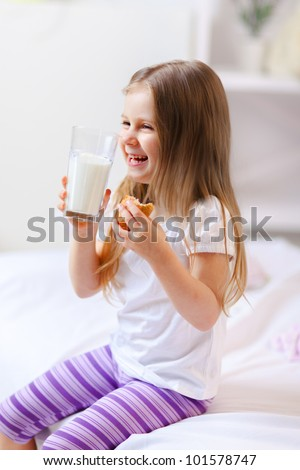 Happy child drinking milk with croissant in bed